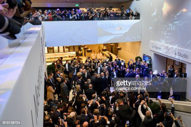 Photographers and journalists take pictures as US President Donald Trump and his delegation are welcomed upon arrival for the World Economic Forum...