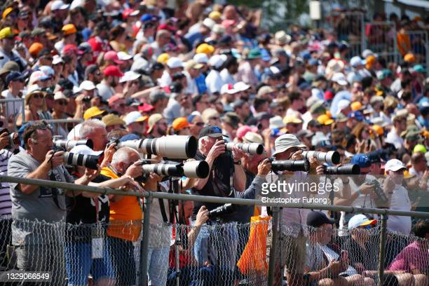 Photographers and motor racing fans soak up the atmosphere during the practice run of the F1 Grand Prix of Great Britain at Silverstone Circuit on...