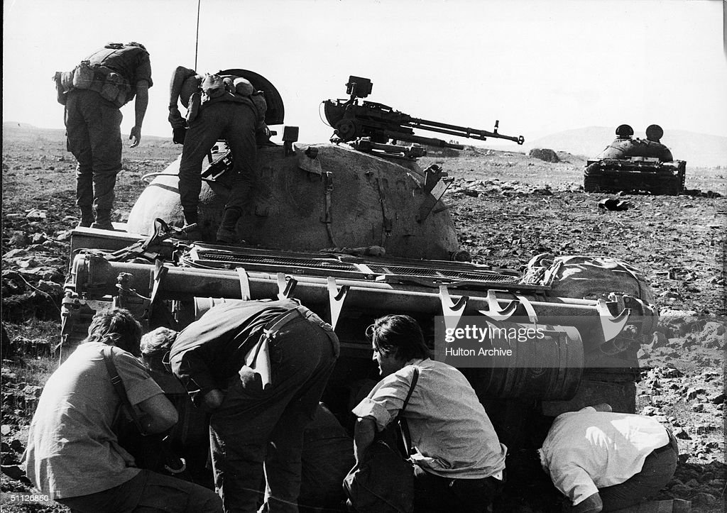 Photographers and radiomen find a wounded Syrian tank crewman hidden under his Soviet-built T-62 tank destroyed by Israelis during the Yom Kippur War, October, 1973. Two Israeli sodliers inspect the turret of the vehicle.