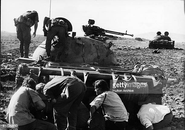 Photographers and radiomen find a wounded Syrian tank crewman hidden under his Soviet-built T-62 tank destroyed by Israelis during the Yom Kippur...