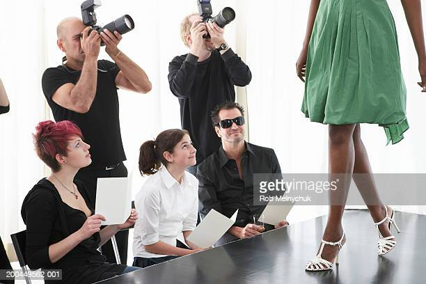 photographers and spectators watching model on runway at fashion show - catwalk stock pictures, royalty-free photos & images