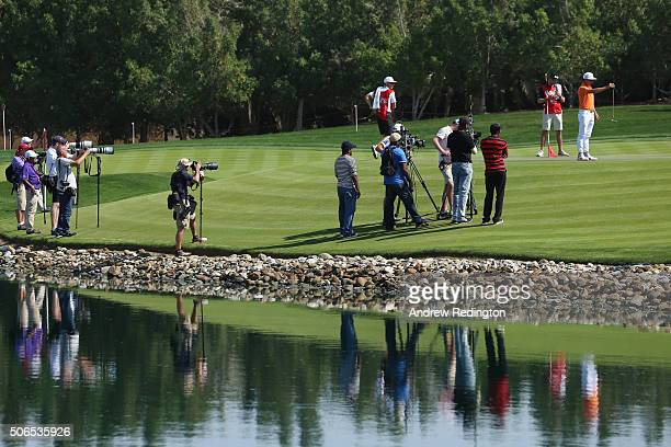 Photographers and TV camaramen focus on Rickie Fowler of the United States as he lines up a putt on the 4th green during round four of the Abu Dhabi...