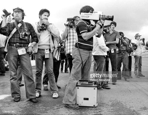 Photographers and TV videographers wait to take photographs of NASCAR cars and drivers during a practice session prior to the start of the 1980...