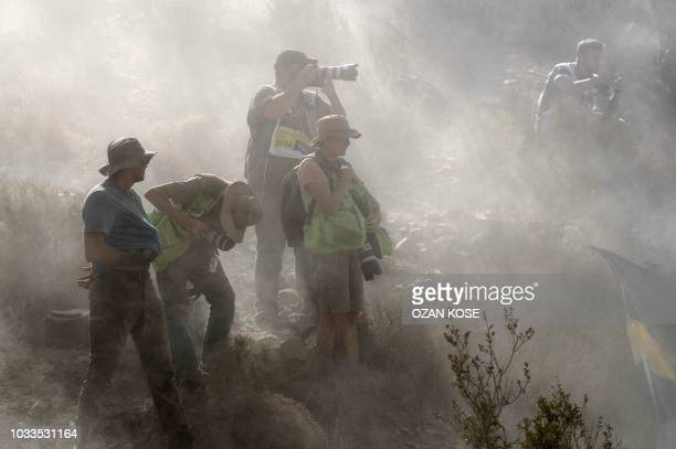 TOPSHOT Photographers are enveloped by clouds of dust after rally cars passed by during the third day of the 2018 FIA World Rally Championship at...