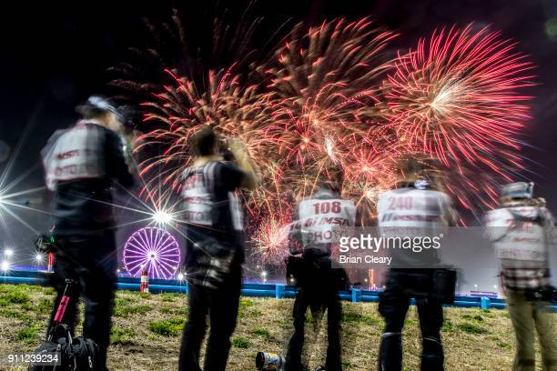 Photographers capture a fireworks display during the Rolex 24 at Daytona at Daytona International Speedway on January 27 2018 in Daytona Beach Florida