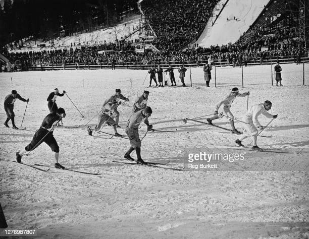 Photographers capturing the competitors at the start of the men's 4x10 kilometre relay event of the 1952 Winter Olympics, watched by spectators in...