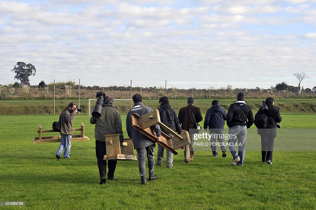 Photographers carry the benches for the set up of the official picture of the Uruguayan national football team on June 2, 2010 in Canelones, Uruguay. AFP PHOTO/Pablo PORCIUNCULA