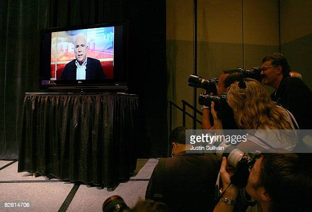 Photographers cover US Sen John McCain broadcasted on a monitor making a statement during a press conference at the at the River Center August 31...