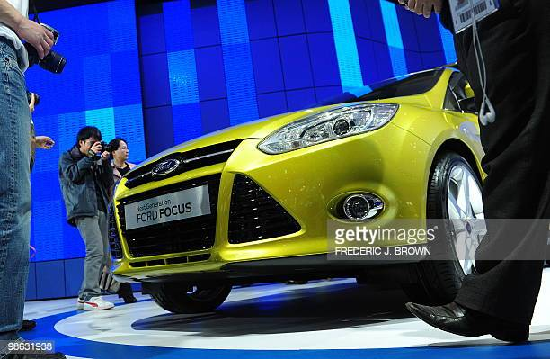 Photographers crowd a Ford Focus during a media preview at the Beijng Auto Show on April 23 2010 Auto sales in booming China hit 1364 million in 2009...