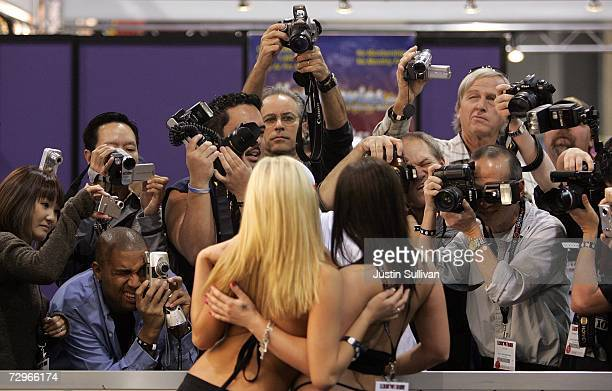 Photographers crowd around two porn actresses as they pose during the 2007 AVN Adult Entertainment Expo at the Sands Convention Center January 10...