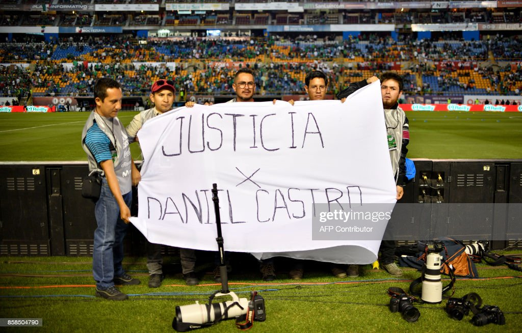 Photographers display a banner to protest against the murder of Mexican photojournalist Edgar Daniel Castro before the 2018 World Cup football qualifier match between Mexico and Trinidad and Tobagoin San Luis Potosi, Mexico, on October 6, 2017. / AFP PHOTO / Yuri CORTEZ