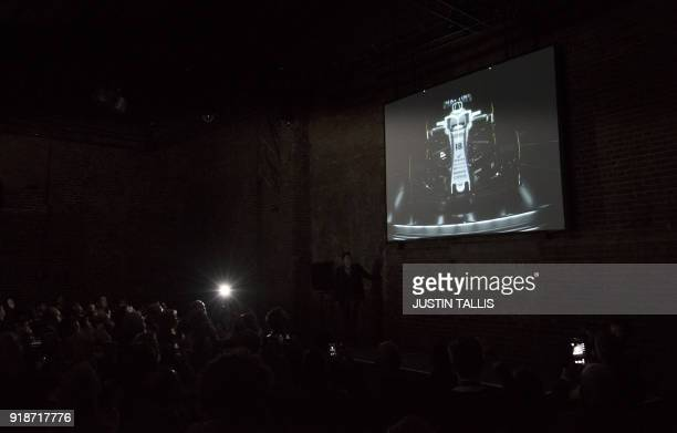 TOPSHOT A photographers flash gun fires as the new car is unveiled on screen during the Williams Formula One 2018 season launch in London on February...