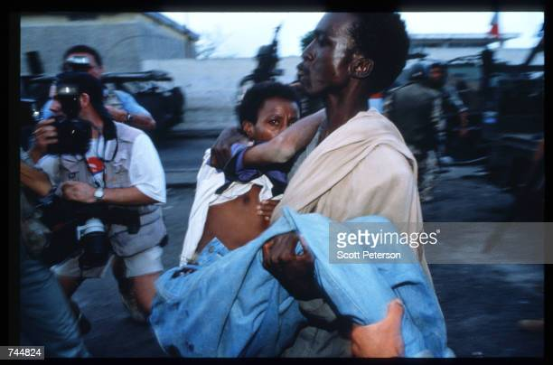 Photographers follow a man carrying another man June 20 1993 in Mogadishu Somalia An estimated 350000 Somalis died due to war famine and disease over...