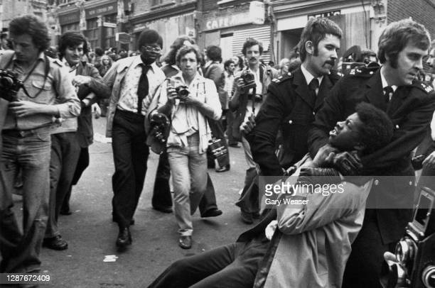 Photographers follow a police officer as he holds a Black demonstrator in a headlock and drags him away, during a National Front march in London,...