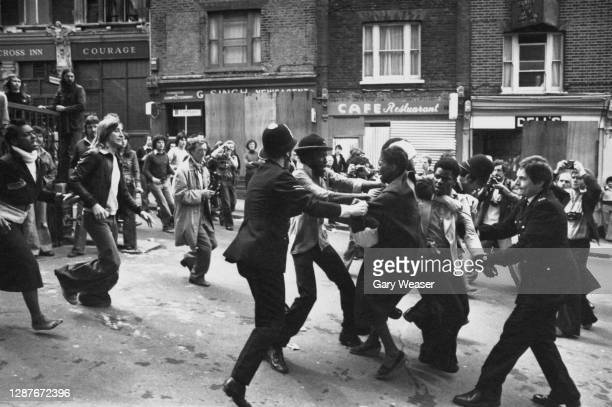 Photographers gather as police officers clash with anti-fascist demonstrator during a National Front march in New Cross, London, England, 12th August...