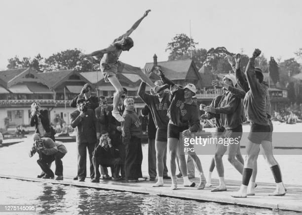 Photographers gather as the American men's eight rowing team throw their cox Ralph Purchase into the River Thames after taking gold in the men's...