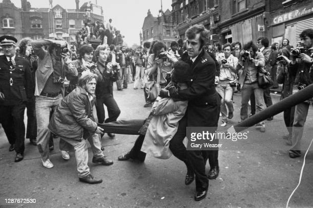 Photographers gather to take shots as a police officer holds a demonstrator in a headlock and drags him away, during a National Front march in...