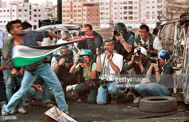 Photographers including James Nachtwey center in white shirt and Heidi Levine at right in helmet take pictures of Palestinians hurling stones at...