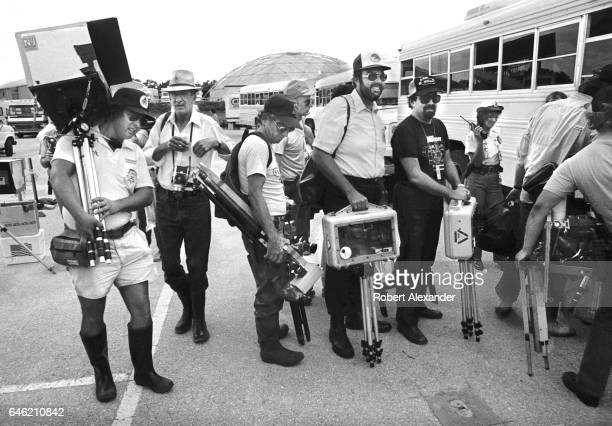 Photographers line up to take a bus to locations where they can set up their soundactivated camera's prior to the launch of the Space Shuttle...