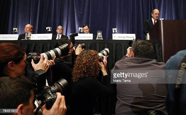 Photographers look on as Former Senator George J Mitchell the lead investigator in Major League Baseball's steroid scandal speaks about the release...
