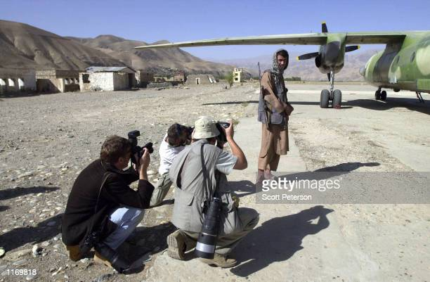 Photographers make pictures of a rebel soldier beside a military plane September 27 2001 in opposition Northern Alliancecontrolled territory of...