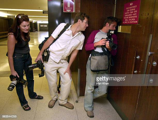 Photographers Michelle Thorpe left of Mirror husband Rupert Thorpe of Daily Mail and Jeff Rayner from Times of London peek through the Central court...