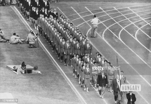 Photographers on the bank beside the running track as the Hungarian team make their entrance, following the flagbearer, at the closing ceremony for...