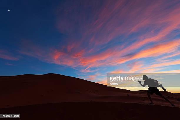 Photographers playing on dunes of desert Sahara at sunset, Morocco