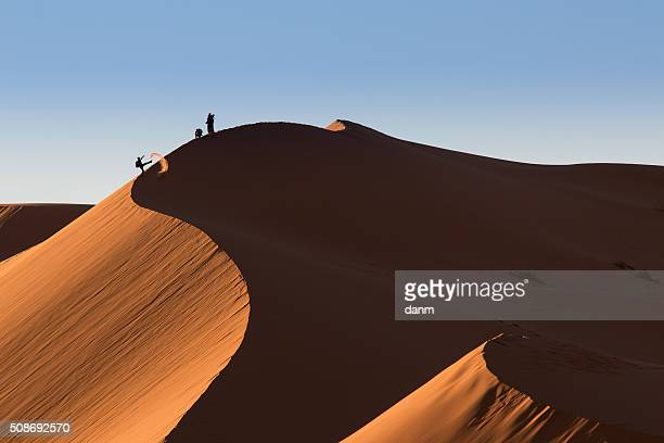 photographers playing on dunes of desert sahara, morocco - ridge stock pictures, royalty-free photos & images