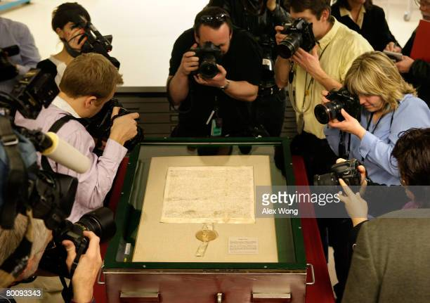 Photographers point their cameras to a 1297 version of Magna Carta during a press viewing of the document at the National Archives March 3 2008 in...