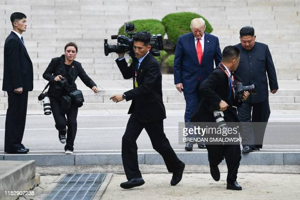 Photographers run as North Korea's leader Kim Jong Un and US President Donald Trump cross south of the Military Demarcation Line that divides North...