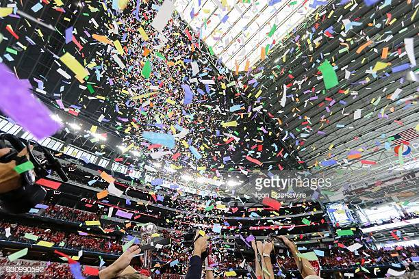 Photographers scramble for a picture with the Goodyear Cotton Bowl Trophy as confetti rains down on the Wisconsin Badgers players celebrating the...