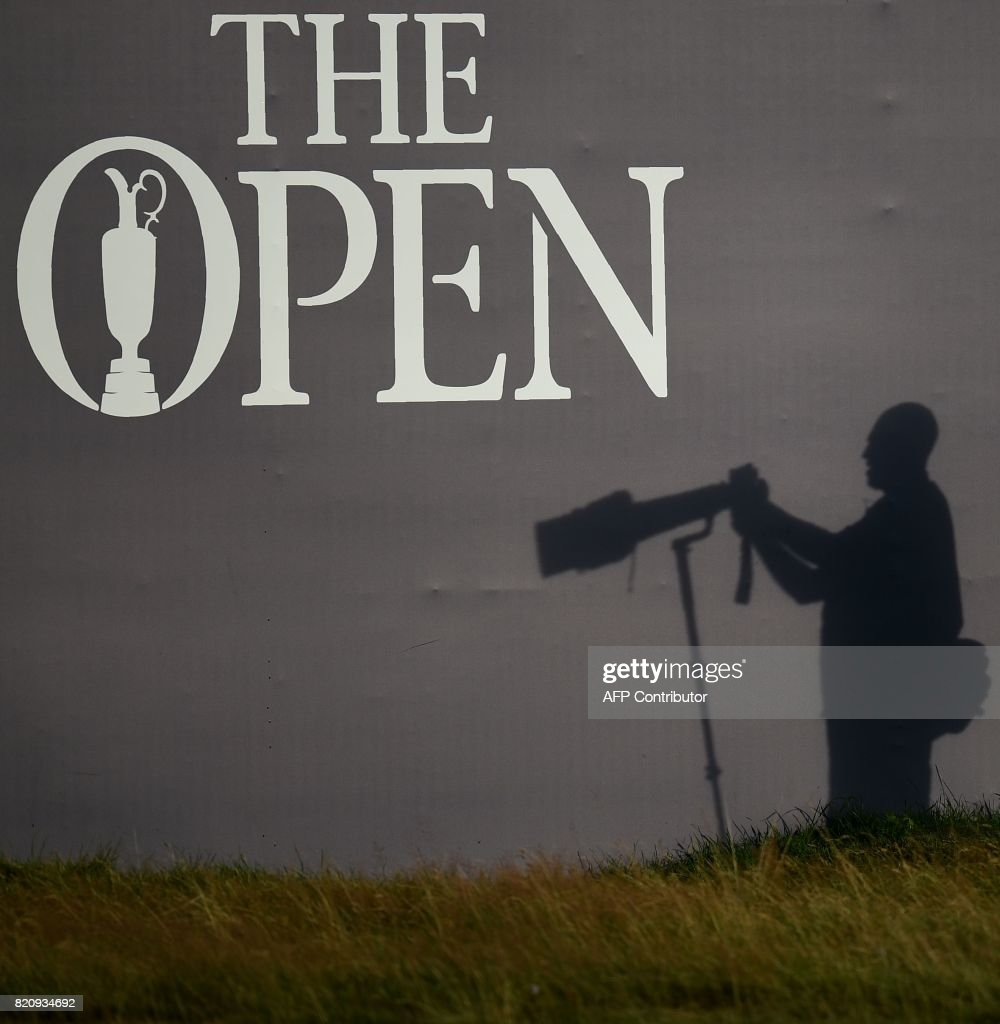 A photographer's shadow is seen beside the 18th green on day three of the Open Golf Championship at Royal Birkdale golf course near Southport in north west England on July 22, 2017. / AFP PHOTO / Oli SCARFF / RESTRICTED