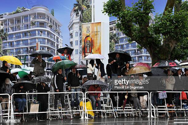 """Photographers shelter from the rain prior to the """"Amour"""" premiere during the 65th Annual Cannes Film Festival at Palais des Festivals on May 20, 2012..."""