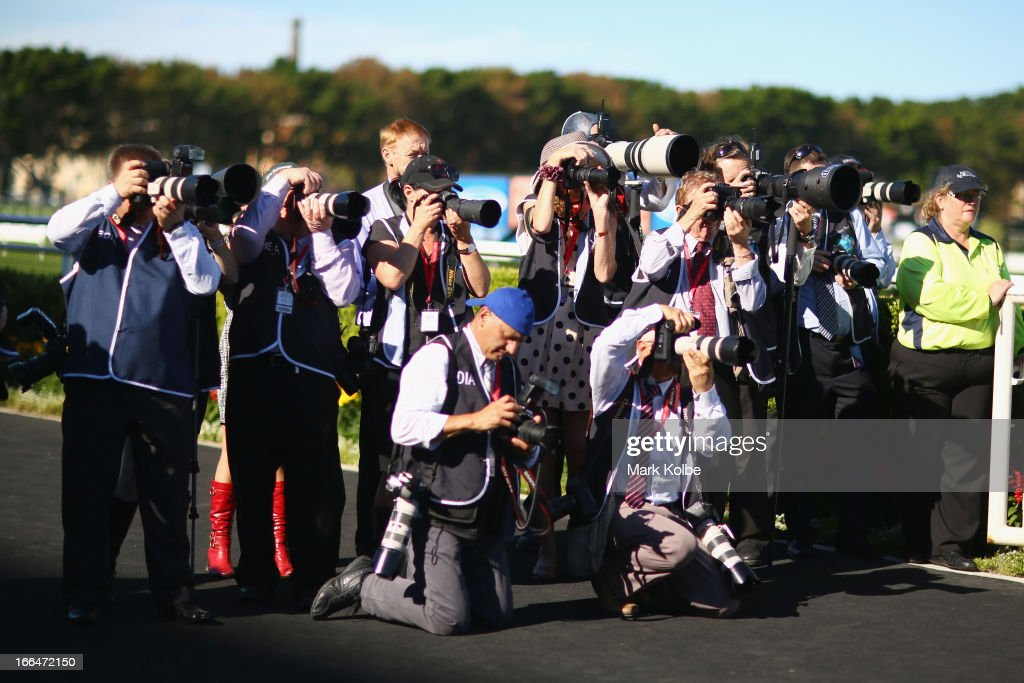 Photographers shoot the winner of a race as they return to the mounting yard on Australian Derby Day at Royal Randwick Racecourse on April 13, 2013 in Sydney, Australia.