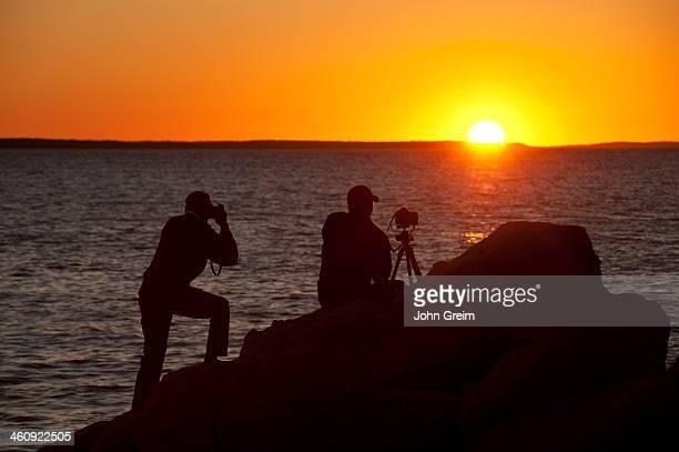 Photographers shooting coastal sunset
