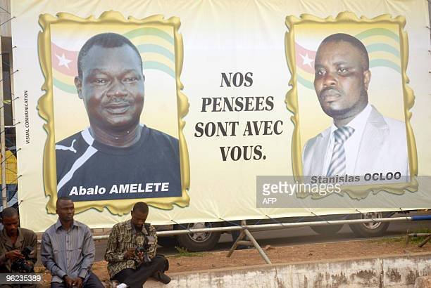 Photographers sit beside a billboard showing portraits of the victims of an attack on the bus carrying the Togo national football team ahead of a...