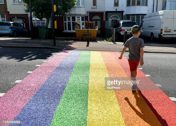 Photographers son crosses the road as London borough of Greenwich show their support to Pride in London by painting a zebra crossing in the rainbow...