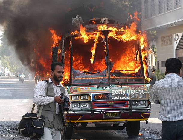 Photographers stand by a burning passenger bus near where a suspected suicide bomber blew himself up at a Shiite mosque during holy Friday prayers...