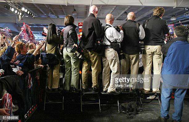 Photographers stand on chairs as they await the arrival of US President George W Bush at a Victory 2004 rally at the Experimental Aircraft...