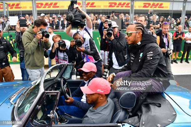 Photographers surround Mercedes' British driver Lewis Hamilton as he sits in a vintage MGC Roadster 1968 ready to be driven by his father Anthony on...