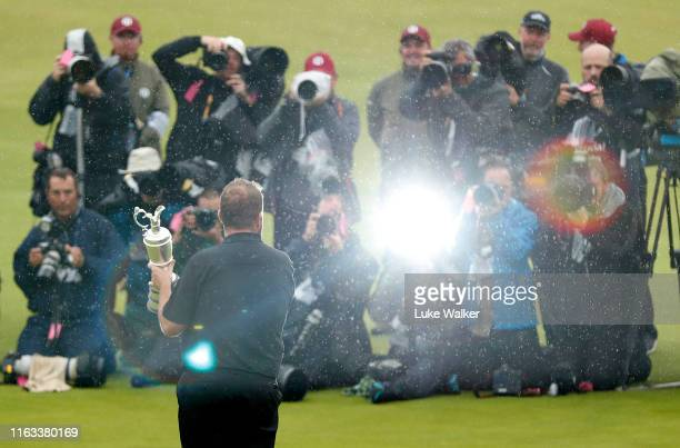 Photographers surround Open Champion Shane Lowry of Ireland as he celebrates with the Claret Jug on the 18th green during the final round of the...