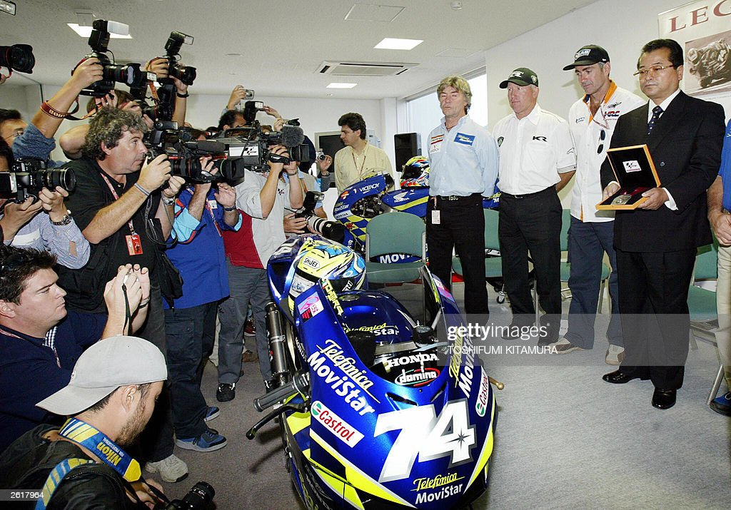 Photographers surround Takashi Kato (R), father of late Japanese world 250cc champion Daijiro Kato, Mick Doohan (2nd R), Kenny Roberts (3rd R) and Angel Nieto (4th R) during a ceremony to honour Kato into the sport's Hall of Fame on the eve of the Pacific Grand Prix at the Twin Ring Motegi 04 October 2003. Organisers announced his racing number 74 was designated as a permanent missing number for the motor sport to honour Kato.