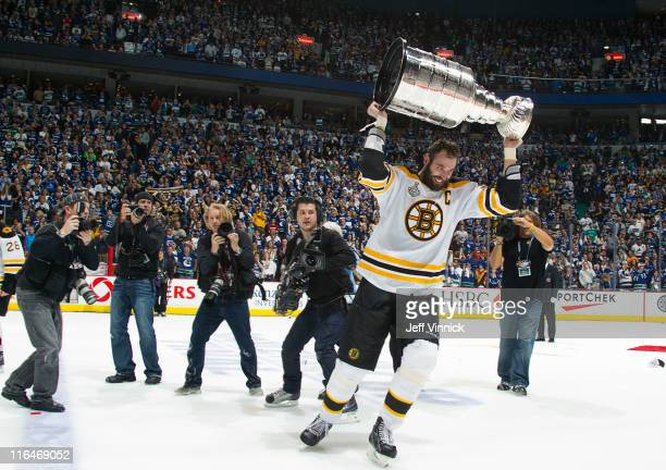 Photographers surround Zdeno Chara of the Boston Bruins as he celebrates with the Stanley Cup after winning Game Seven of 2011 NHL Stanley Cup Final...