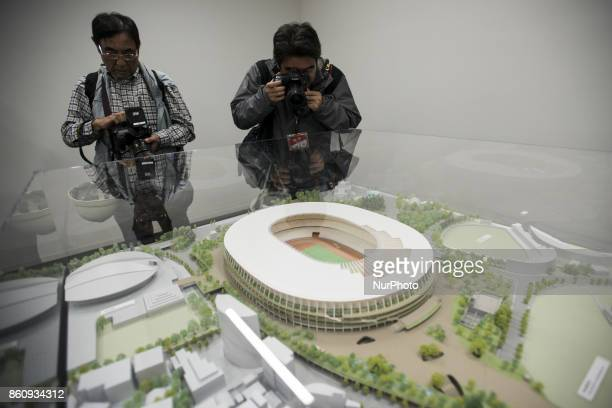 Photographers take a photo of the 1/150 scale model of the new national stadium for the 2020 Olympics during a press preview in Tokyo Oct 13 2017