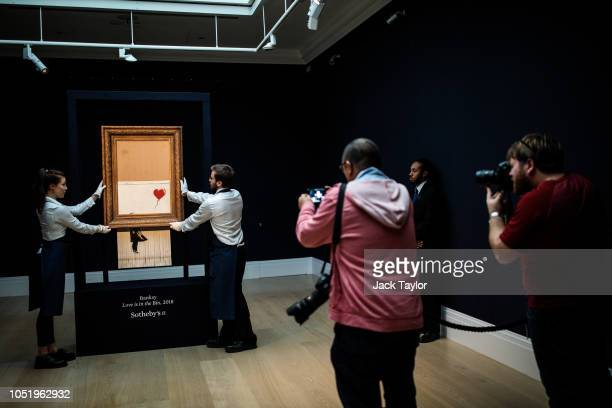 Photographers take capture of 'Love is in the Bin' by British artist Banksy during a media preview at Sotheby's auction house on October 12 2018 in...