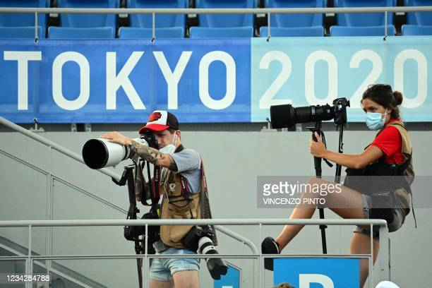 Photographers take images during the Tokyo 2020 Olympic Games men's singles quarterfinal tennis match between France's Ugo Humbert and Russia's Karen...