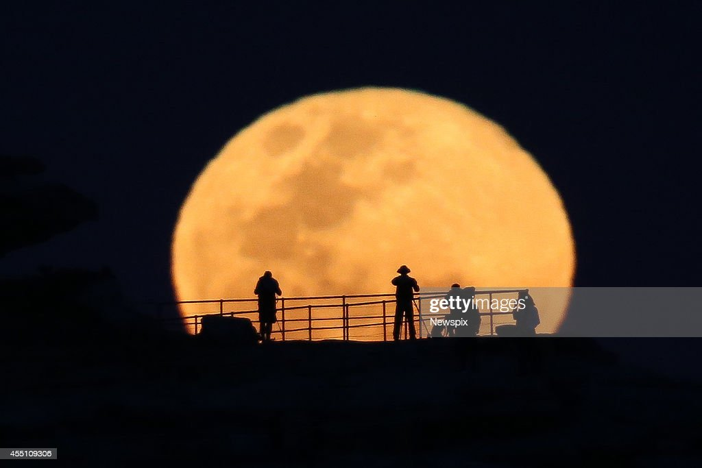 Photographers take images of the full supermoon, as it rises over North Bondi headland on September 9, 2014 in Sydney, Australia. A supermoon or harvest moon involves a full moon coinciding with it's closest approach to the Earth on it's elliptical orbit.