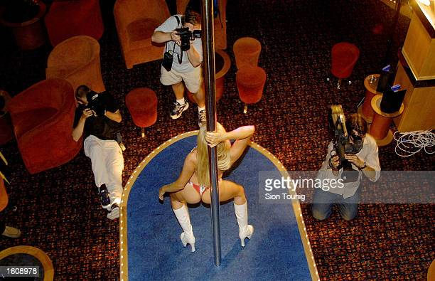 Photographers take photographs of a member of the World Record Pole Dancing Team August 14 2001 at the For your Eyes Only Club in London United...