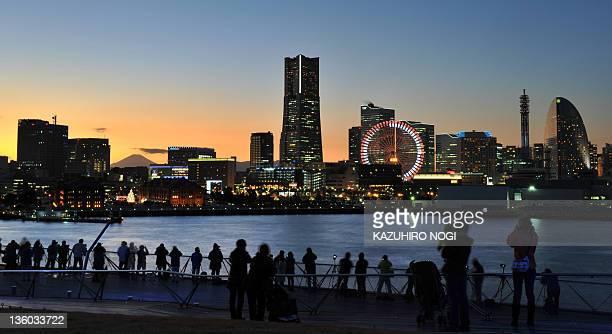 Photographers take photographs of the Yokohama Landmark Tower and other amusement parks at Minato Mirai 21 a new urban development in Yokohama on...